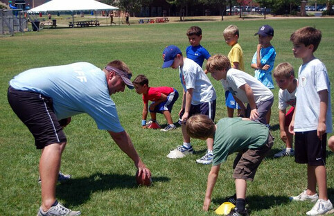 A coach teaches the basics of the game to children in the playground