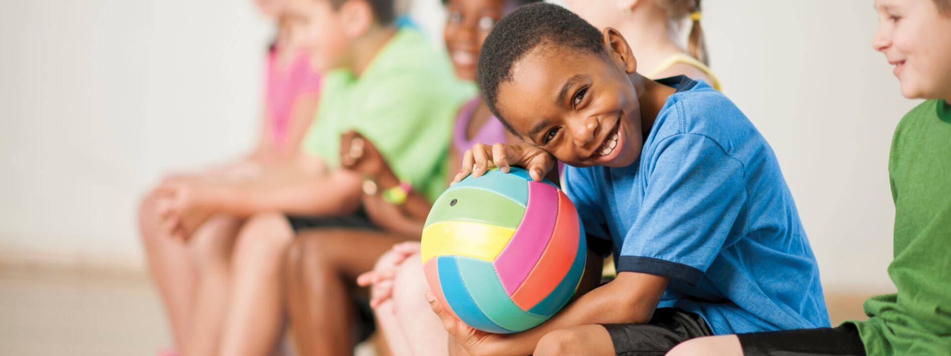 A boy with a volleyball on his lap at YMCA of Greater Charlotte