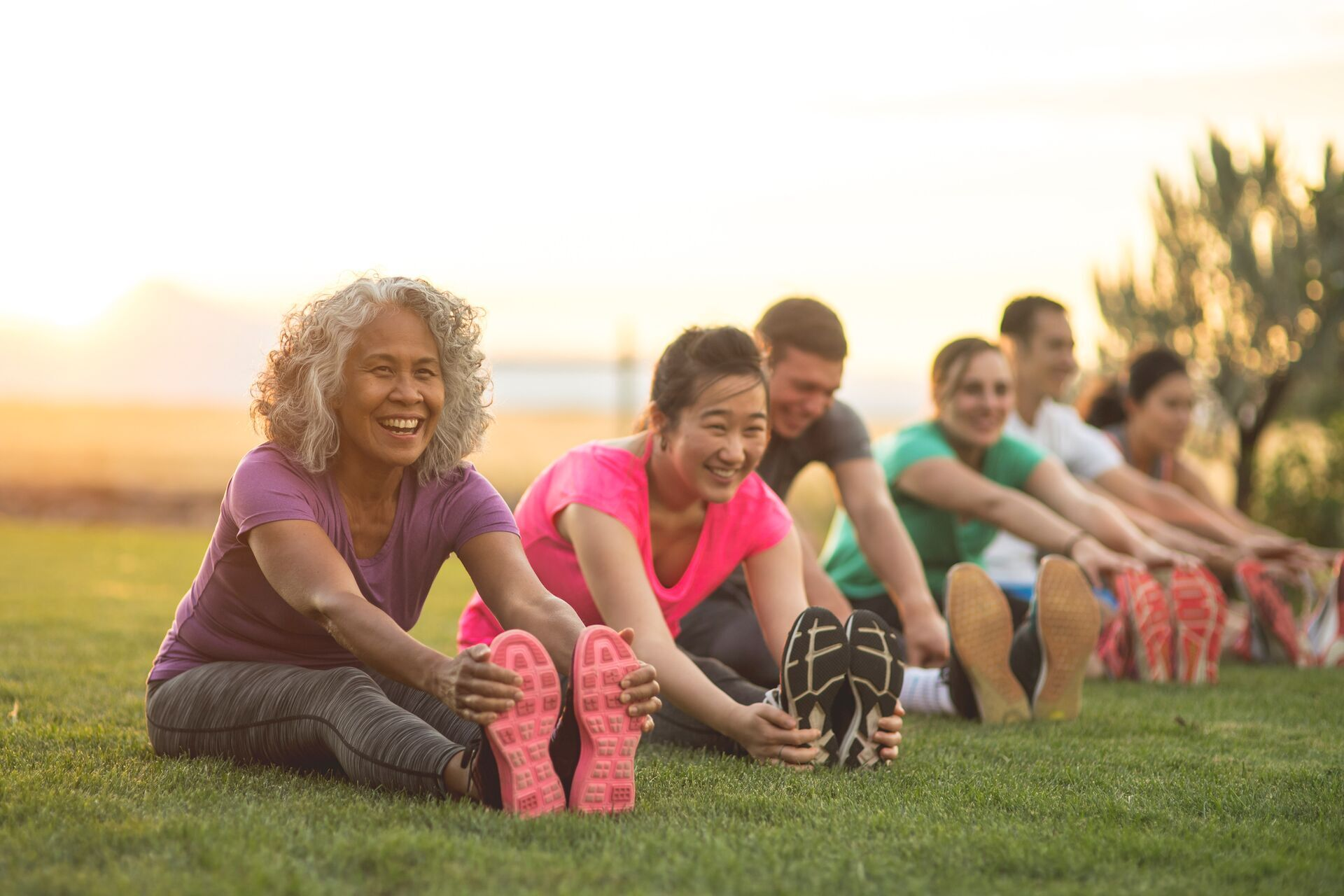 A group of adults attending a fitness class outdoors are doing leg stretches. The participants are arranged in a line. The focus is on a mature ethnic woman who is smiling toward the camera.