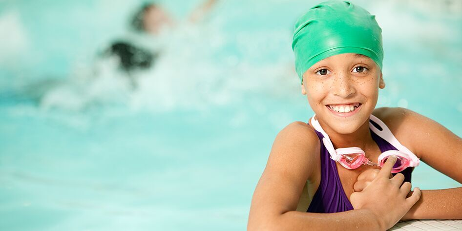 water safety image of child on the edge of a pool smiling with arms crossed