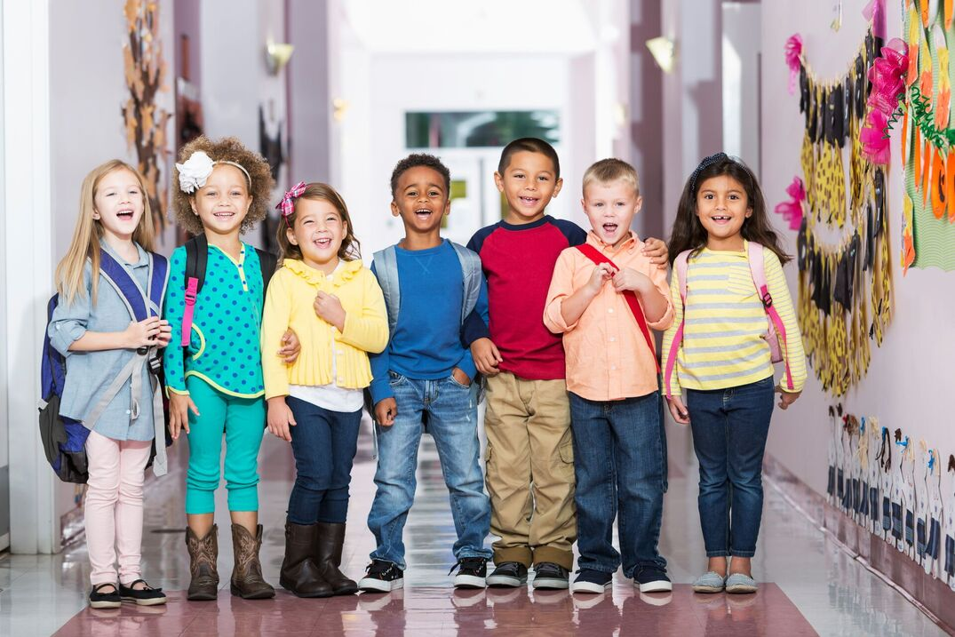 A multi-ethnic group of seven children standing in a row in a school hallway, laughing and smiling at the camera. The little boys and girls are kindergarten or preschool age, 4 to 6 years.