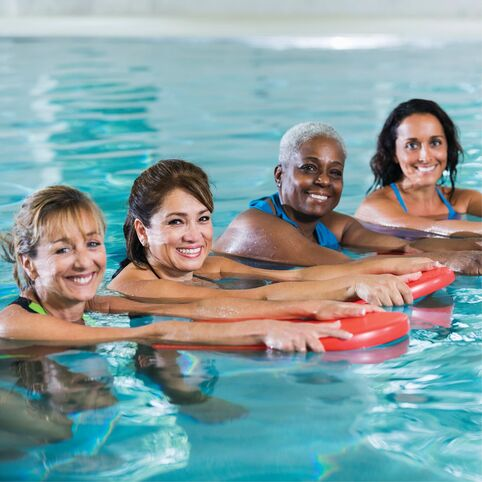 Four women participating in YMCA water fitness classes