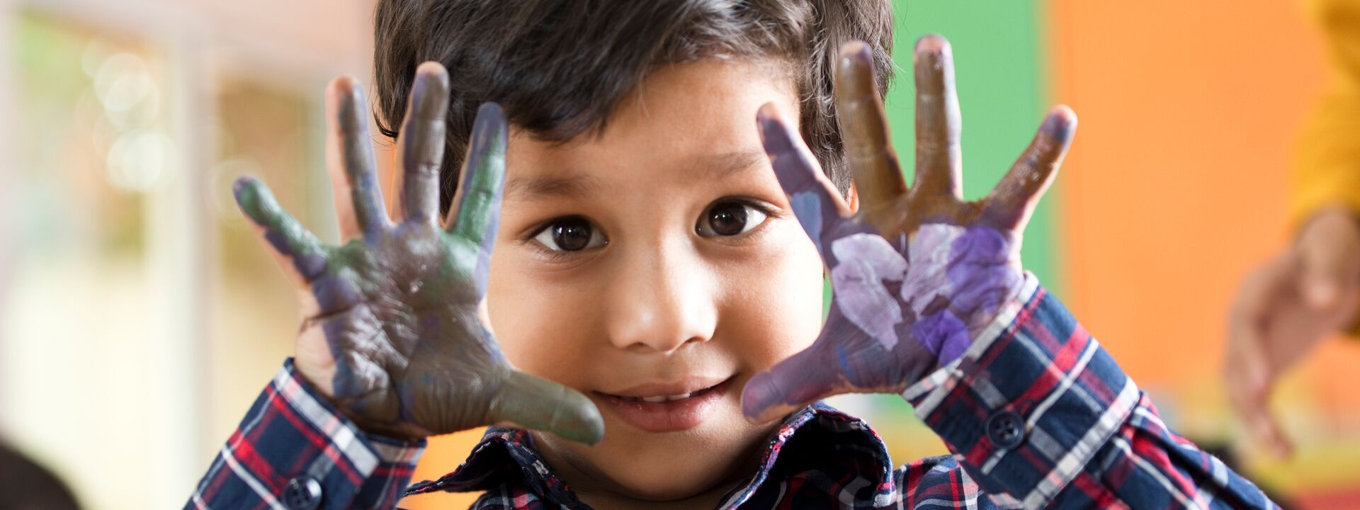Preschool boy showing his painted palm of hands