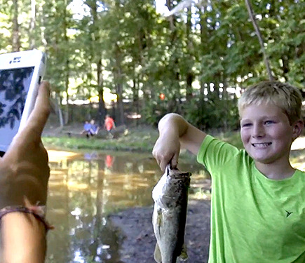 A boy with a fish in his hand at YMCA of Greater Charlotte adventure day camp