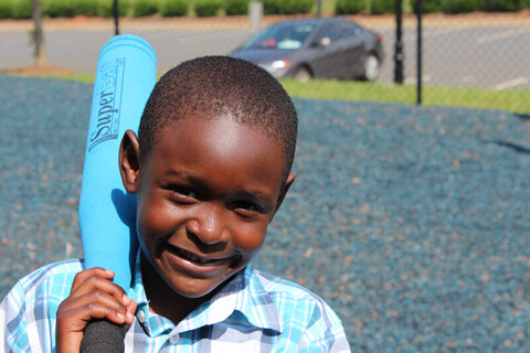 A boy smiling with a baseball bat in his hand