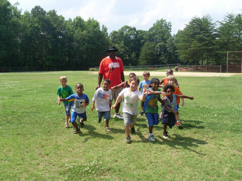 Cute little children running along with the coach at YMCA of Greater Charlotte