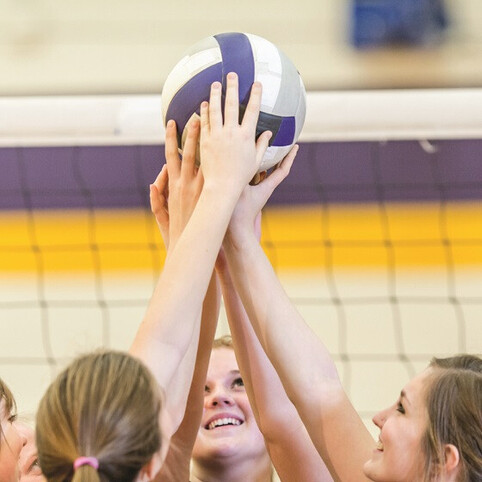 Girls holding a volleyball high above their heads at YMCA of Greater Charlotte