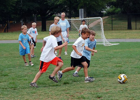 Children playing with a soccer ball at YMCA soccer summer day camp