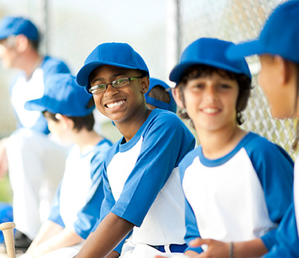 Boys wearing baseball team dress with a cap at YMCA Greater Charlotte