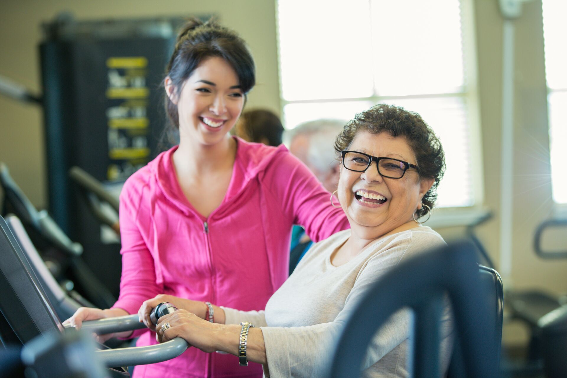 Beautiful Hispanic senior woman confidentlly uses machine at gym or senior center. Young female personal trainer helps the senior woman. They are both smiling. People are working out it the background.