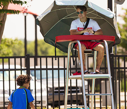 A lifeguard watches a kid walking by