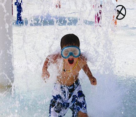 A boy splashing in the water and having fun at YMCA of Greater Charlotte