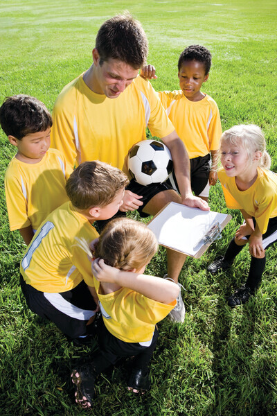 Coach with team of children playing soccer, 5 and 6 year old boys and girls