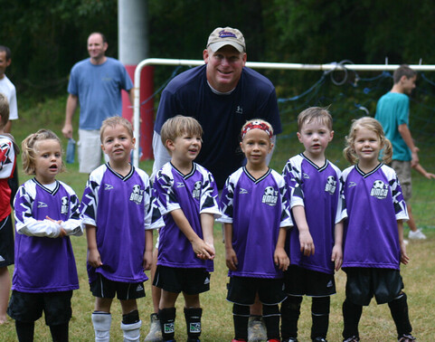 Little kids with their coach having fun at YMCA recreational soccer