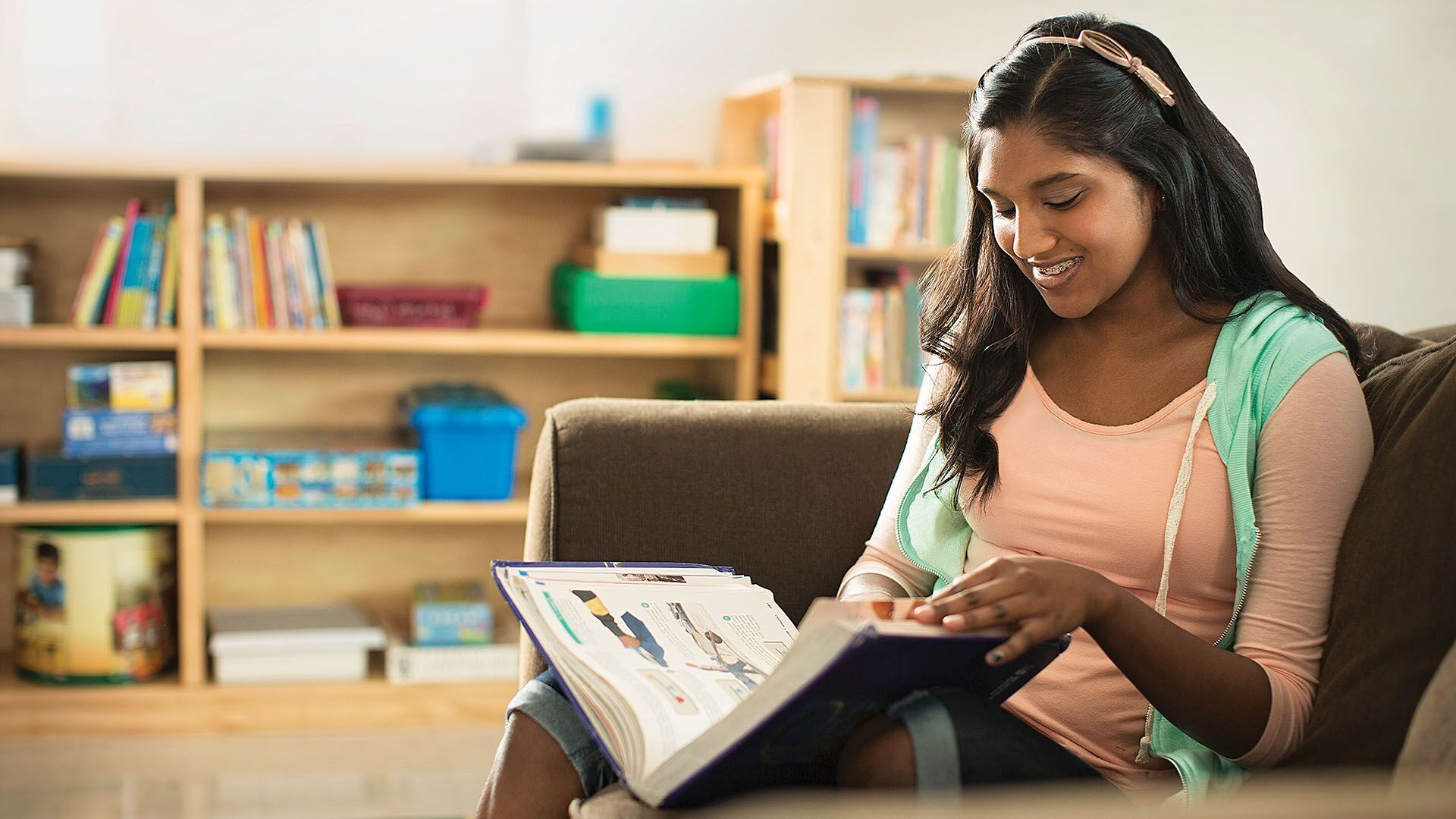 A girl sitting on a sofa reads a book in the life learning program at YMCA Greater Charlotte