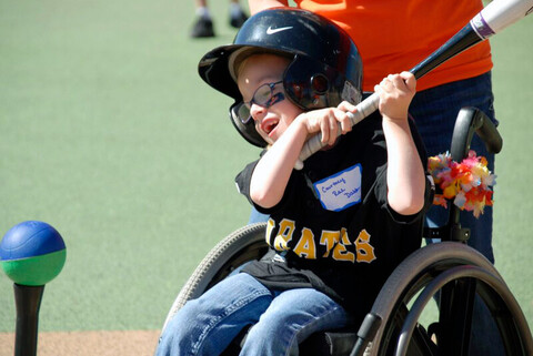 A disabled boy hitting a baseball from his wheelchair at the YMCA of Greater Charlotte