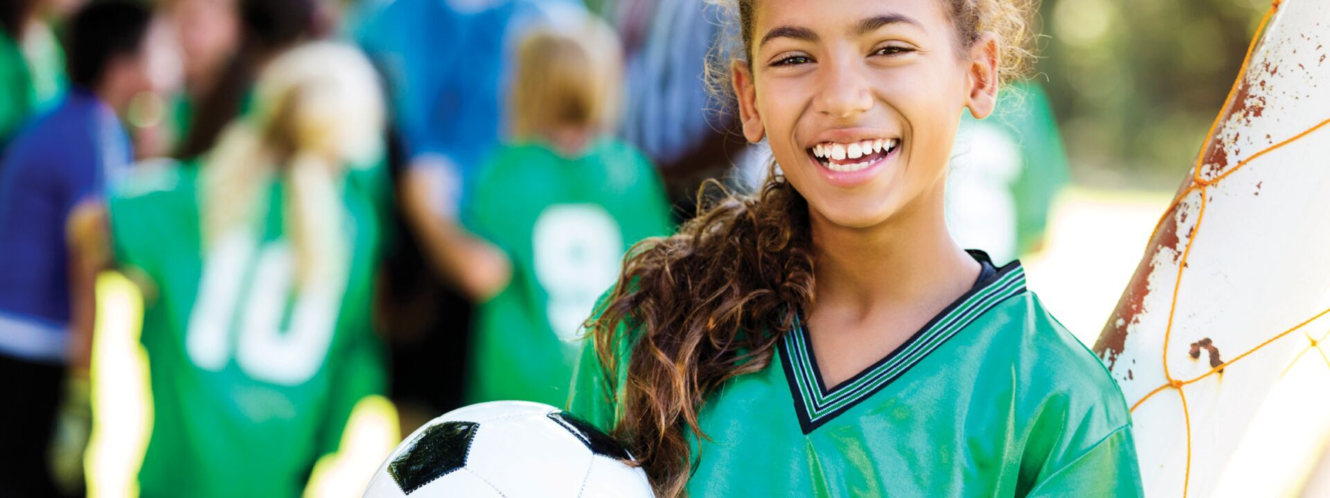 A girl with a soccer ball in her hand at YMCA recreational soccer